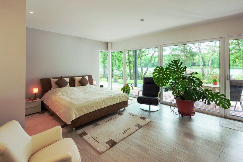 Chambre et grande baie vitrée Maison en ossature bois par Weberhaus ...