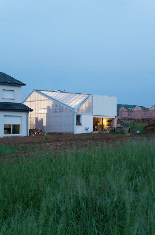 Maison contemporaine atypique et sa toiture en tuiles for Hangar jardin
