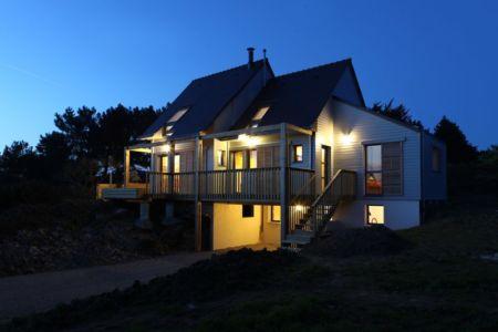 façade garage de nuit - Maison bois bioclimatique par Patrice Bideau architecte