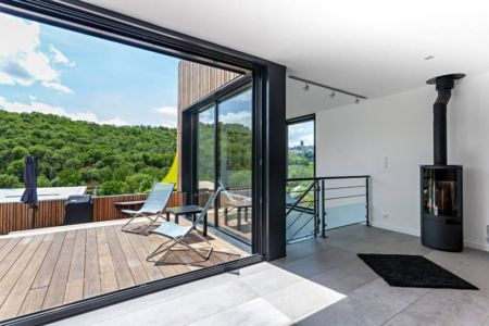 balcon & poêle à bois design - maison bois par Hugues Tournier - Cardaillac, France