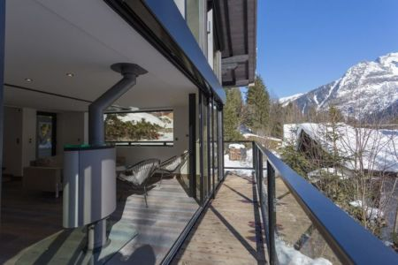 balcon ouvert sur salon, poêle à bois- chalet-dag par Chevalier Architectes - Chamonix, France