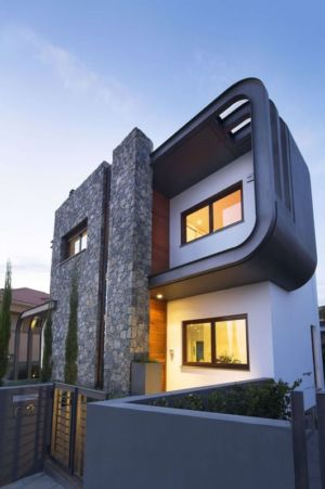 façade arrière pierre et béton illuminée - tsikkinis par Tsikkinis Architecture Studio - Limassol, Chypre