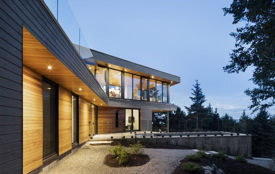 Grande résidence en bois en forme V bordant une rivière au Canada ...